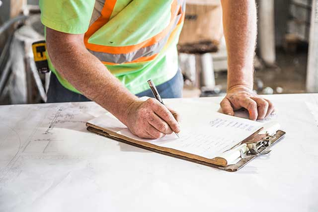 construction worker signing papers on a table