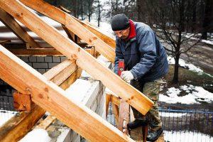 man repairing roof in winter