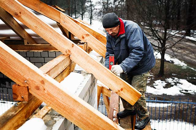 man repairing roof in winter