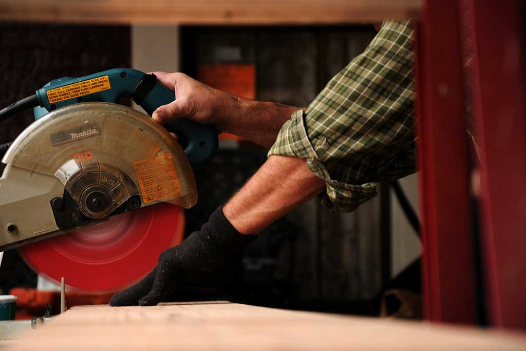 Construction worker using saw on wood plank