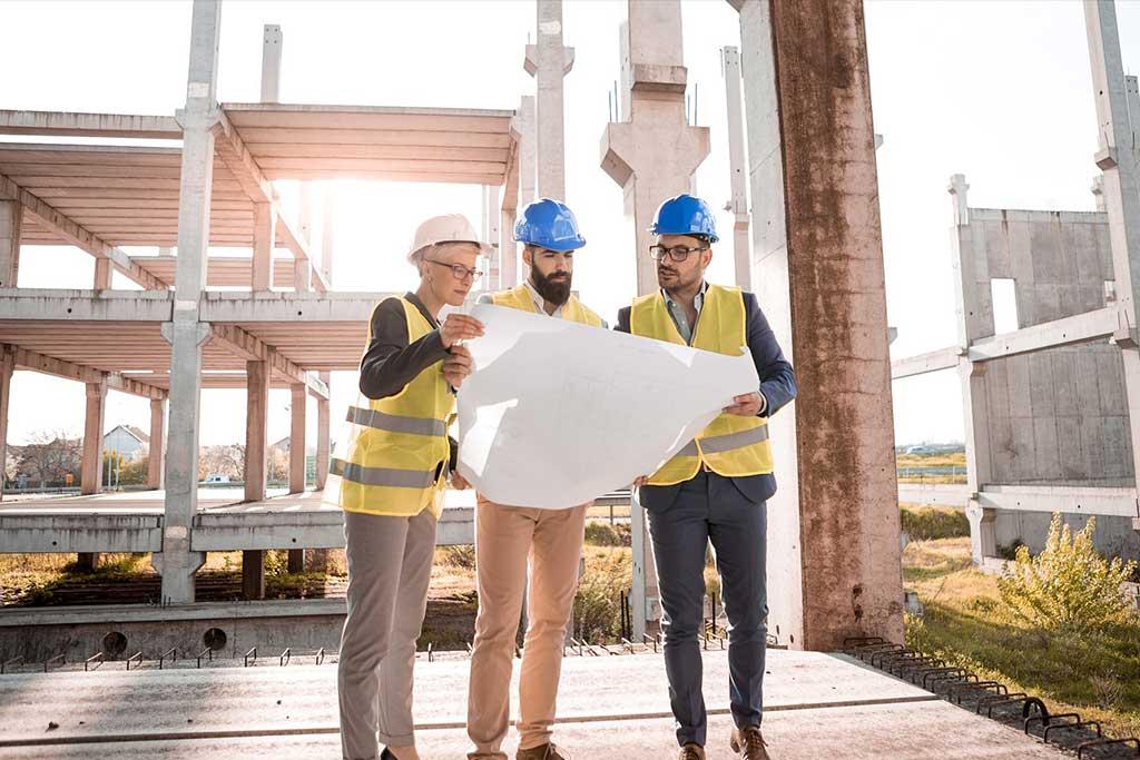 Construction personnel reviewing blueprints for construction build